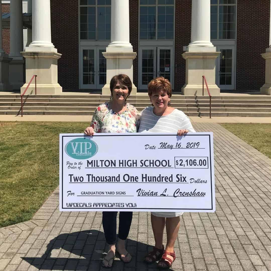 Milton parent holding 2019 high school graduation yard sign fundraiser check