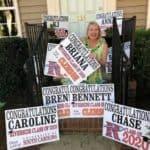 Riverside parent holdings high school graduation yard signs