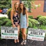 high school senior Faith and Ashlyn in yard with graduation signs