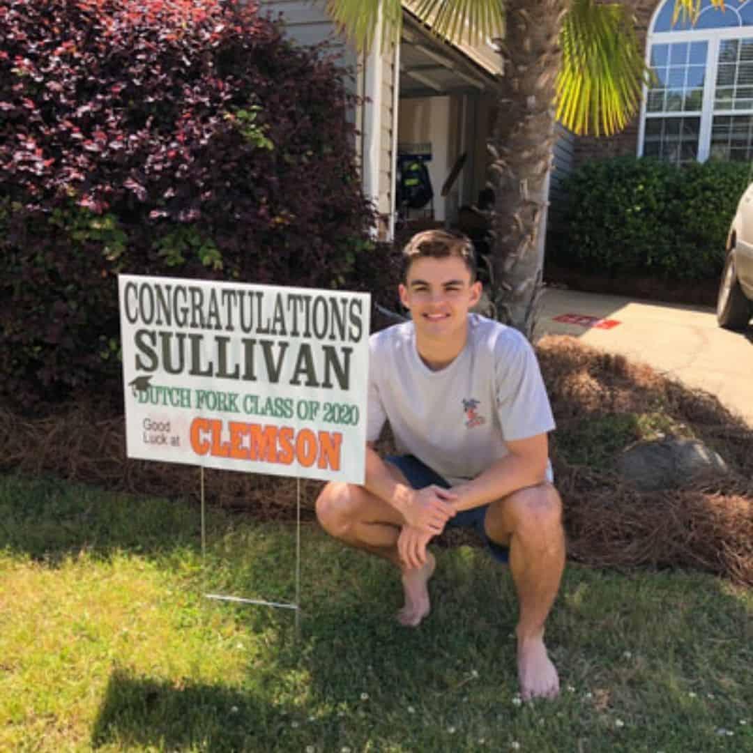 high school senior Sullivan in yard with graduation signs